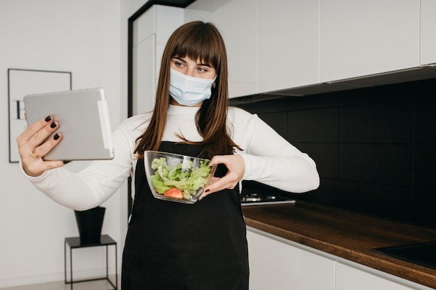 Weibliche bloggerin, die sich mit tablette beim vorbereiten des salats aufzeichnet