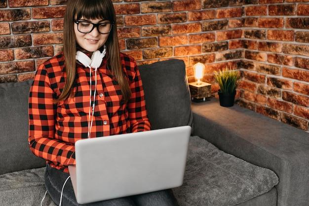 Weibliche bloggerin mit kopfhörern, die online mit laptop streamen
