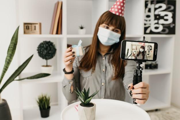 Weibliche bloggerin mit medizinischer maske, die geburtstag mit smartphone strömt