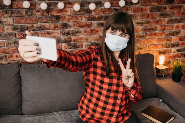 Weibliche bloggerin mit medizinischer maske, die online mit smartphone strömt