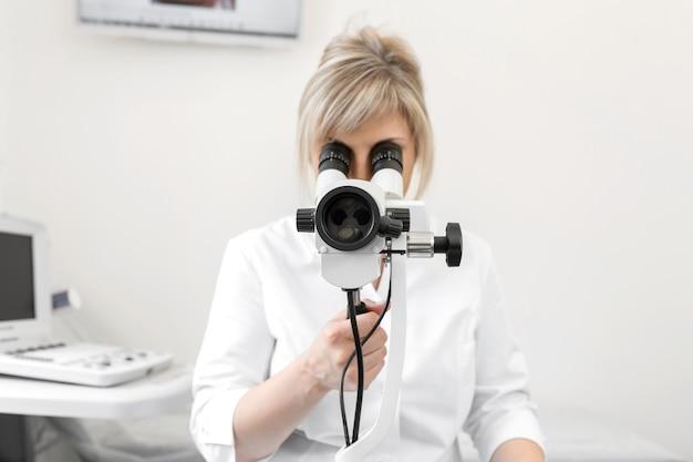 Weibliche blonde ärztin gynäkologin schaut durch ein kolposkop