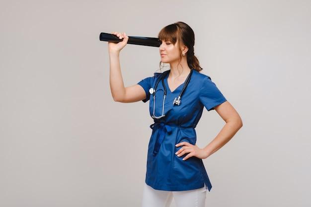 Weibliche brünette ärztin, die tomographie-röntgenfilm betrachtet.