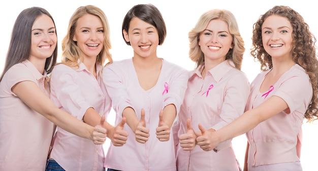 Weibliche brustkrebsteilnehmer, die oben daumen gestikulieren.