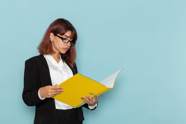 Weibliche büroangestellte der vorderansicht, die gelbe datei auf blauer oberfläche hält und liest