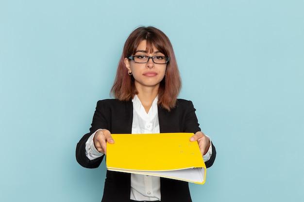 Weibliche büroangestellte der vorderansicht, die gelbe datei auf der blauen oberfläche hält