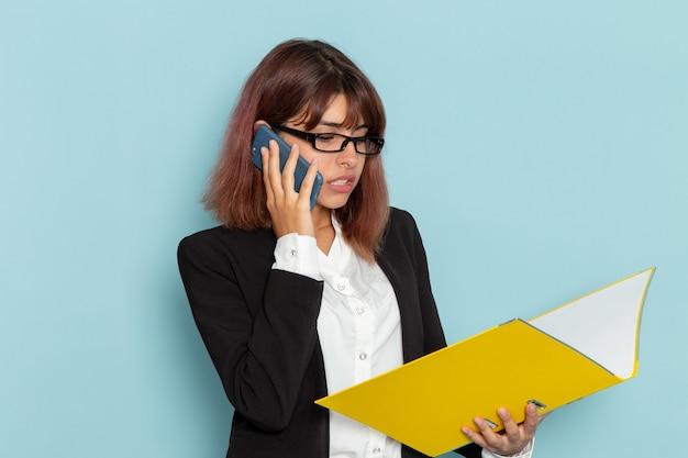 Weibliche büroangestellte der vorderansicht, die gelbes dokument hält und am telefon auf blauer oberfläche spricht