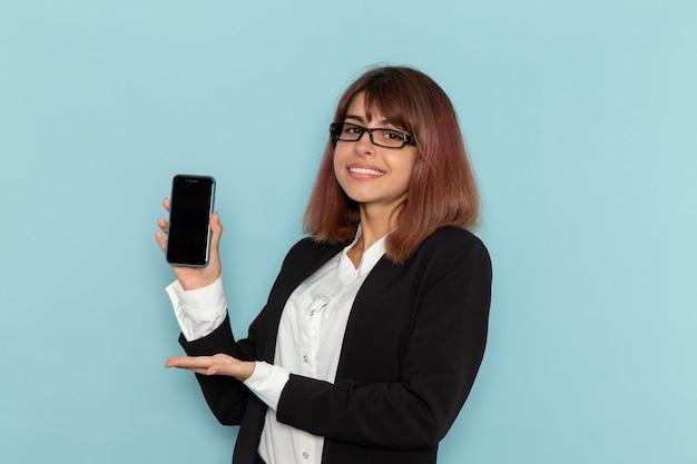 Weibliche büroangestellte der vorderansicht, die ihr smartphone auf blauer oberfläche hält