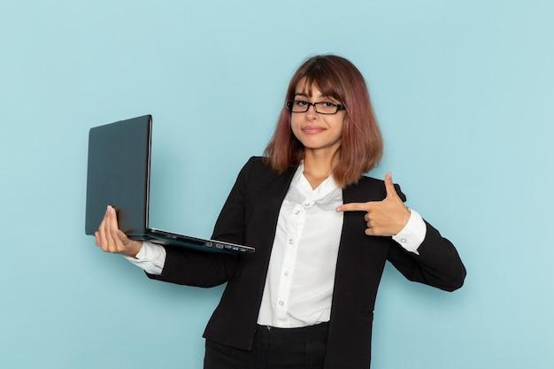Weibliche büroangestellte der vorderansicht, die ihren laptop auf der blauen oberfläche hält