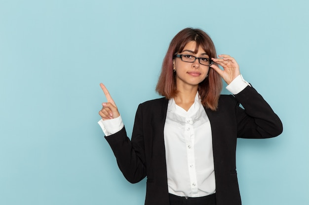 Weibliche büroangestellte der vorderansicht, die in der schwarzen jacke auf der blauen oberfläche aufwirft