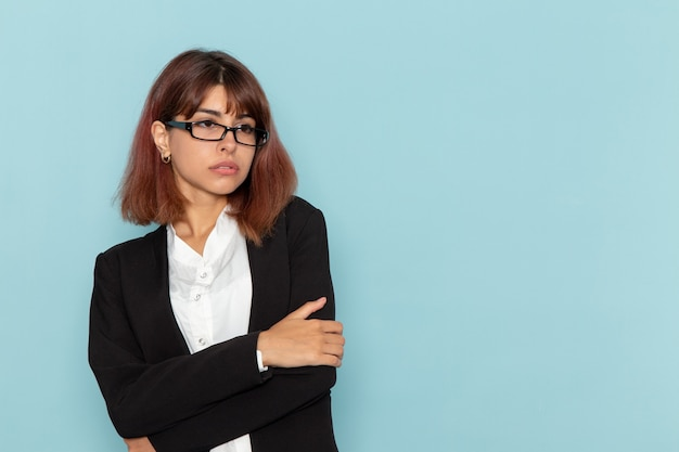 Weibliche büroangestellte der vorderansicht im strengen anzug, der auf der blauen oberfläche aufwirft