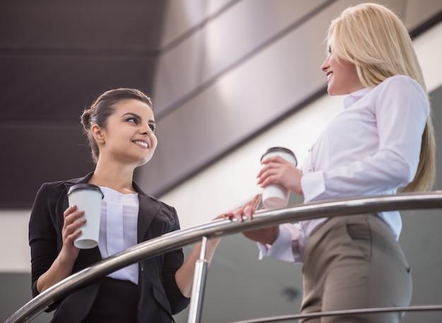 Weibliche büroangestellte, die während der kaffeepause sprechen.