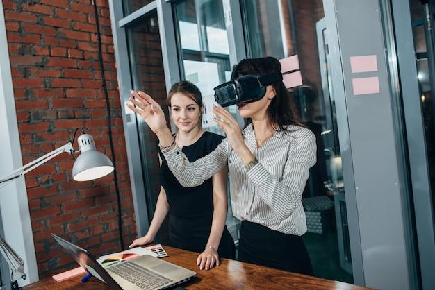 Weibliche büroangestellte haben spaß bei der arbeit und schauen sich 3d-videos in vr-brillen an.