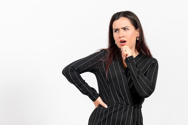 Weibliche büroangestellte im strengen schwarzen anzug, der auf weiß aufwirft und denkt