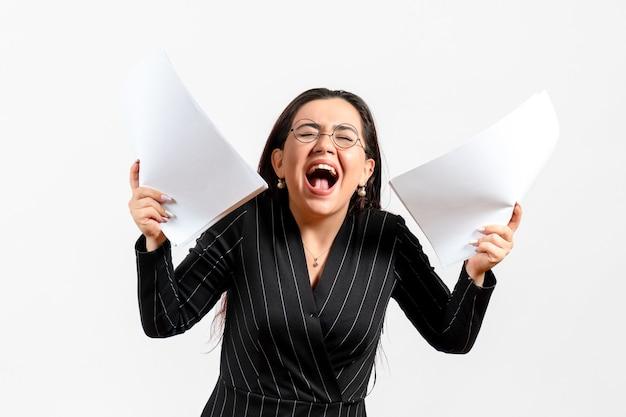 Weibliche büroangestellte im strengen schwarzen anzug, der dokumente hält, die auf weiß schreien