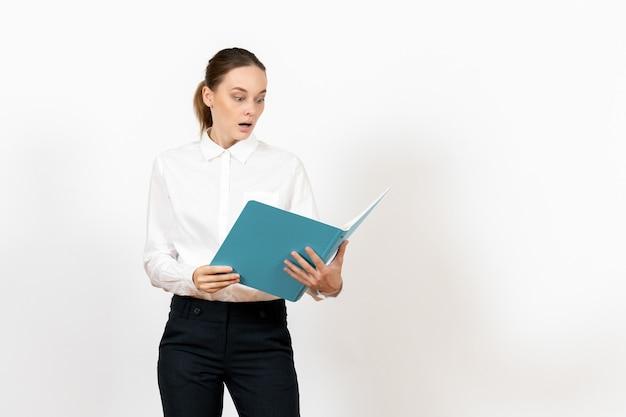 Weibliche büroangestellte in der weißen bluse, die blaue datei auf hellweiß hält und liest