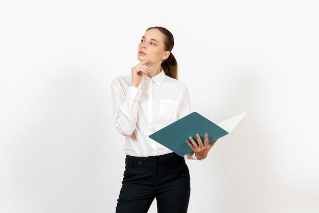 Weibliche büroangestellte in der weißen bluse, die blaue datei auf weiß hält und liest