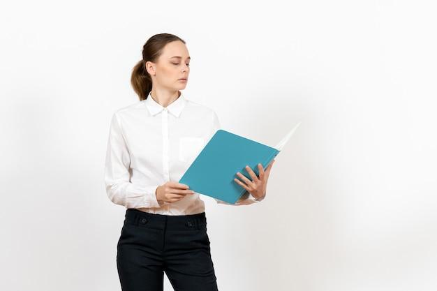 Weibliche büroangestellte in der weißen bluse, die blaue datei auf weiß hält