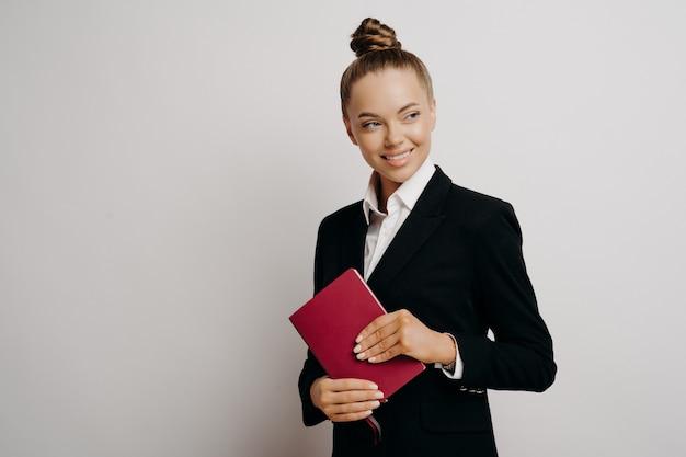 Weibliche büroangestellte in formellem outfit mit haaren im brötchen, die nach rechts schauen und lächeln, während sie ein rotes notizbuch hält, das wichtige geschäftsinformationen enthält und isoliert vor grauem hintergrund steht