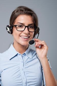 Weibliche call-center-agentin posiert mit kopfhörern mit mikrofon