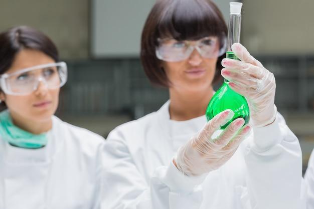 Weibliche chemiker, die grüne flüssigkeit betrachten