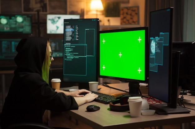 Weibliche cyberkriminelle, die auf computer mit grünem bildschirm tippen. unternehmens-hacking.