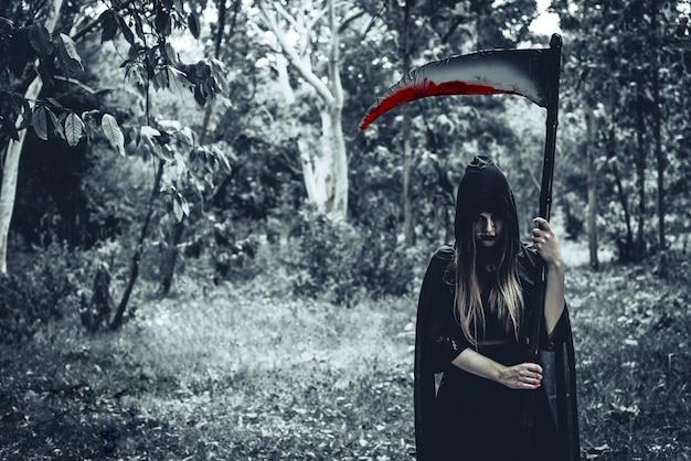 Weibliche dämonenhexe mit dem blutigen sensenmann, der vor geheimniswaldhintergrund steht
