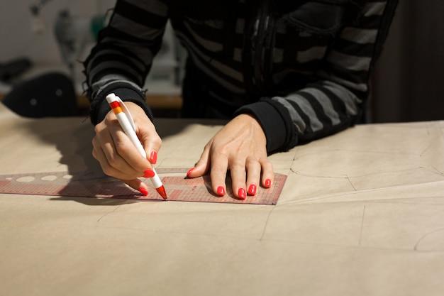 Weibliche damenschneiderin übergibt schneidermarkierungszeichnung auf kraftpapier für die herstellung von mustern