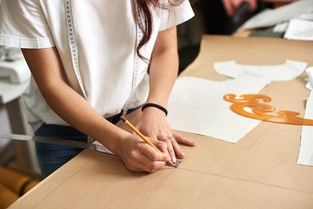 Weibliche designerhände machen zeichenlinien auf karton