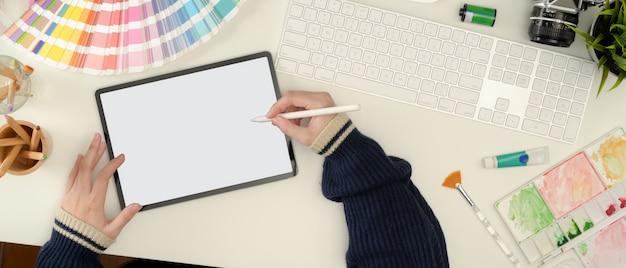Weibliche designerin, die an mock-up-tablette mit stift auf weißem arbeitstisch mit malwerkzeugen arbeitet