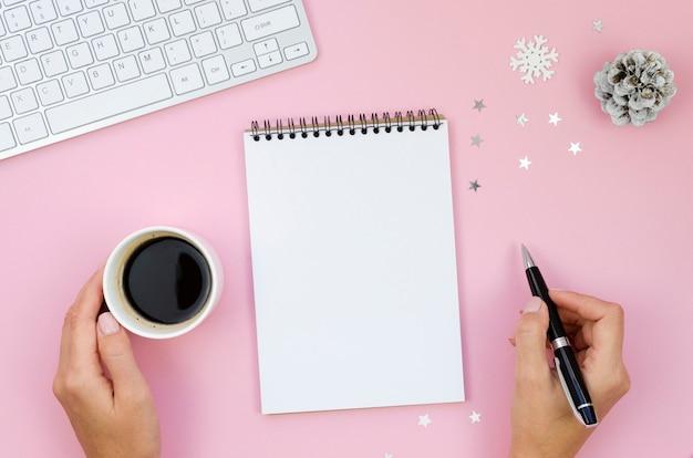 Weibliche draufsicht winterarbeitsplatzmodell mit notizbuch und zeigern, tastatur und weihnachtsdekoration