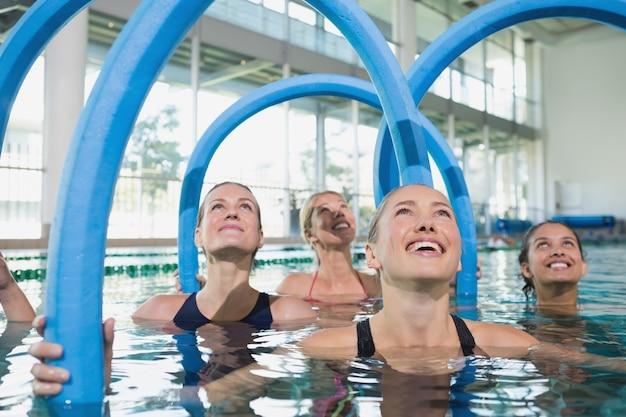 Weibliche eignungklasse, die aqua aerobic mit schaumrollen tut