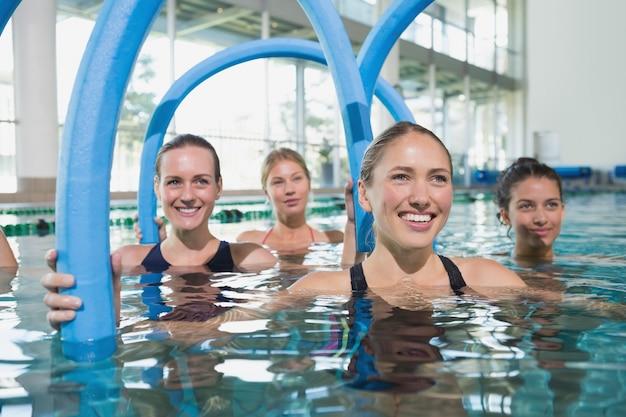 Weibliche eignungsklasse, die aquaaerobic mit schaumstoffrollen tut