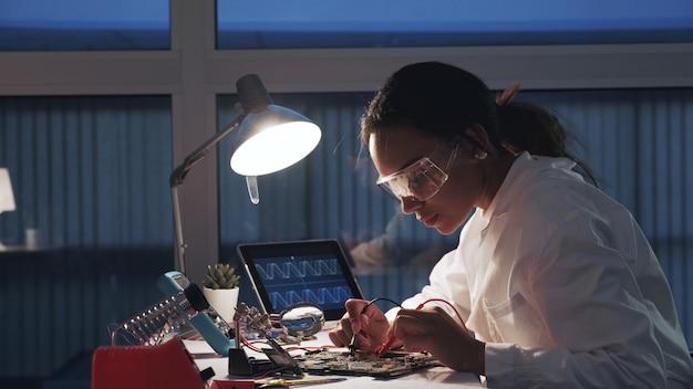 Weibliche elektronikingenieurin, die mit multimetertester und anderen elektronischen geräten im labor arbeitet