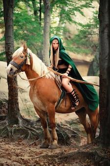 Weibliche elfe im wald mit ihrem pferd