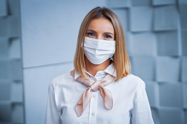 Weibliche empfangsdame, die aufgrund von covid-19-beschränkungen gesichtsmaske trägt
