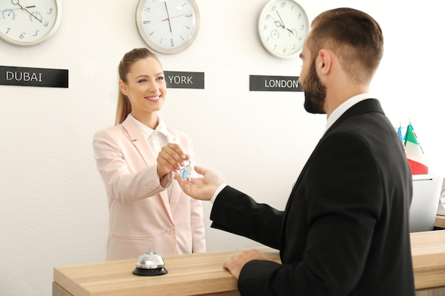 Weibliche empfangsdame, die zimmerschlüssel an kunden im hotel übergibt