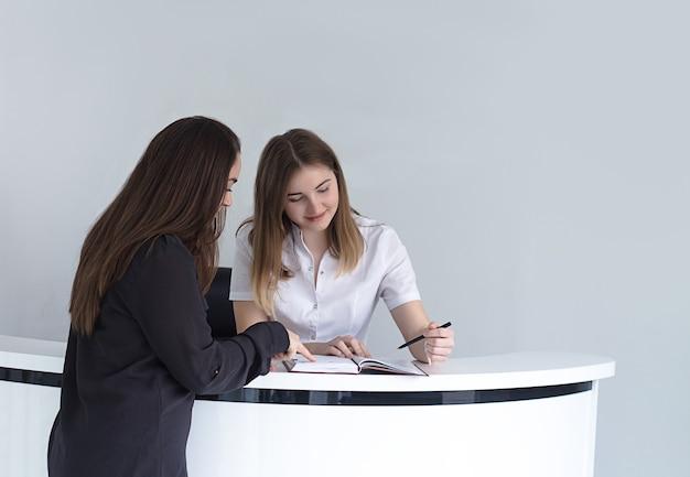 Weibliche empfangsdame in der medizinischen klinik, die den zeitplan mit dem patienten bespricht und aufzeichnungen schreibt