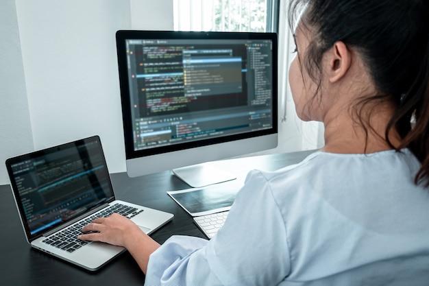 Weibliche entwicklerprogrammiererin, die an der codierung von programmsoftware-computern arbeitet, website- und entwicklungsdatenbanktechnologie im büro schreibt.