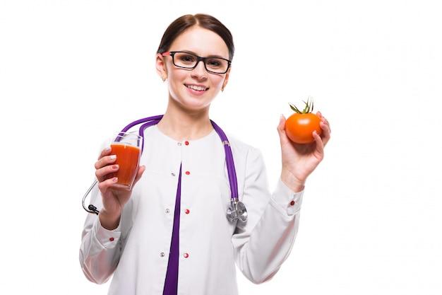 Weibliche ernährungswissenschaftler-grifftomate im abschnitt und glas saft in ihren händen auf weiß