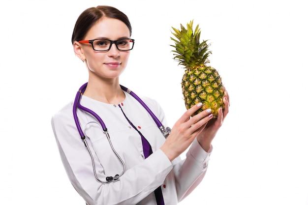 Weibliche ernährungswissenschaftlergriffananas in ihren händen auf weiß