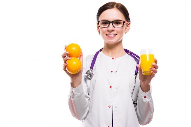 Weibliche ernährungswissenschaftlergrifforangen und glas frischer saft in ihren händen