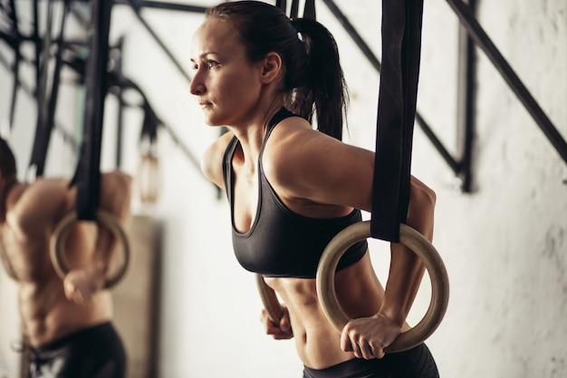 Weibliche erwachsene, die klimmzüge an der stange im cross-fit-trainingsstudio machen