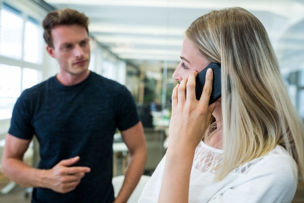 Weibliche exekutive sprechen über handy, während sie mit kollegen interagieren