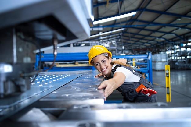 Weibliche fabrikarbeiterin in schutzuniform und helm, die industriemaschine an der produktionslinie betreibt
