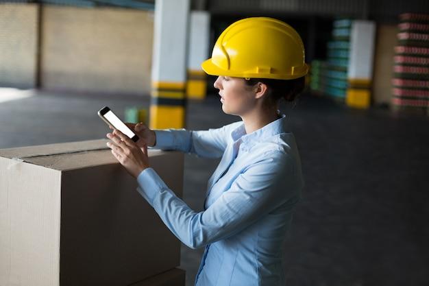 Weibliche fabrikarbeiterin mit handy