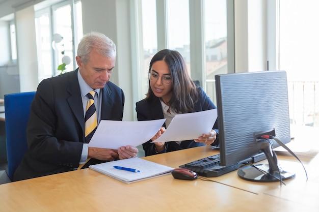 Weibliche fachkraft, die dem klienten am arbeitsplatz dokumentdetails erklärt. seriöser unternehmensleiter, der finanz- oder rechtsexperten berät. teamwork oder kooperationskonzept
