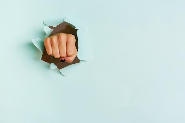 Weibliche faust, die durch hintergrund des blauen papiers locht. krieg, kampf, konflikt, feministisches konzept.