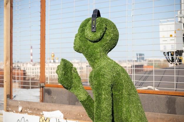 Weibliche figur bedeckt mit künstlichem grünem gras mit kopfhörern im profil - loft-projekt floors etagi, sankt petersburg, russland, april 2021