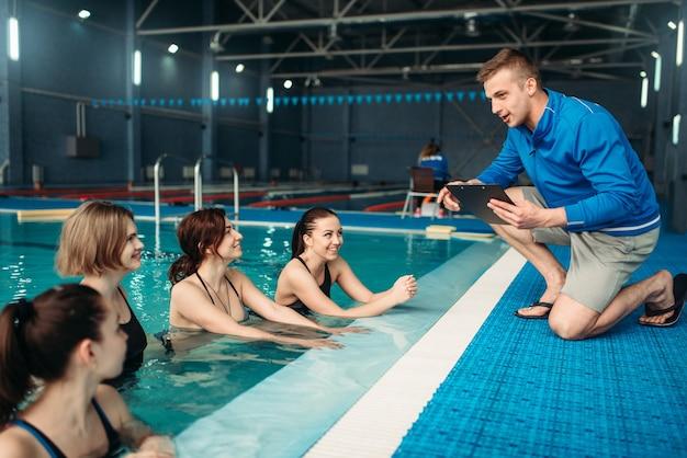 Weibliche fitnessklasse mit trainer, aqua-aerobic