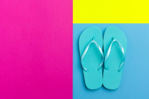 Weibliche flipflops auf einem farbblockhintergrund